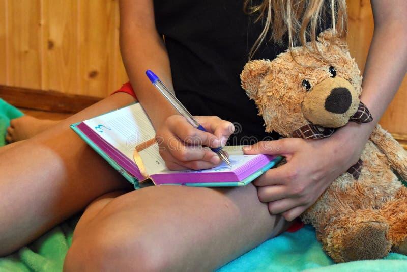 A menina bonita escreve o diário fotos de stock