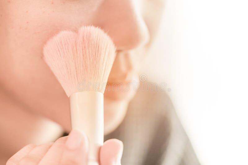A menina bonita está aplicando-se cora no mordente pela escova imagens de stock