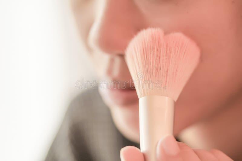 A menina bonita está aplicando-se cora no mordente pela escova imagem de stock