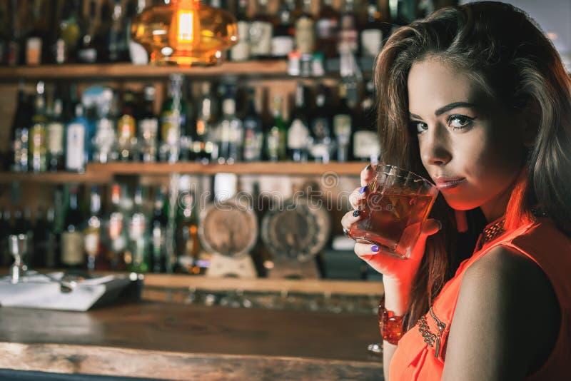A menina bonita está bebendo um cocktail com o vapor do gelo na barra foto de stock