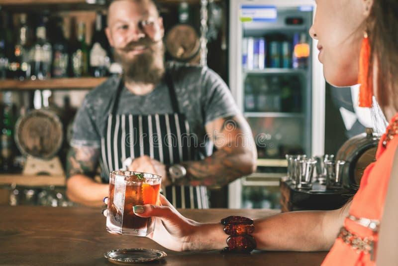 A menina bonita está bebendo um cocktail com o vapor do gelo na barra imagens de stock royalty free
