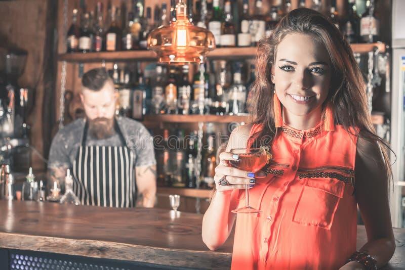 A menina bonita está bebendo um cocktail com o vapor do gelo na barra foto de stock royalty free