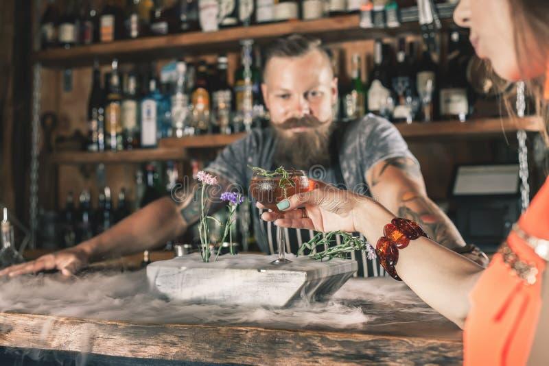 A menina bonita está bebendo um cocktail com o vapor do gelo na barra imagem de stock