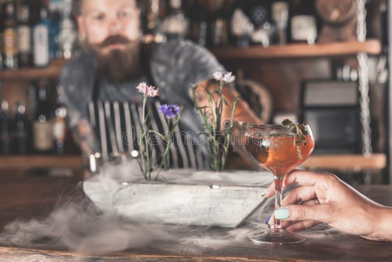 A menina bonita está bebendo um cocktail com o vapor do gelo na barra fotografia de stock