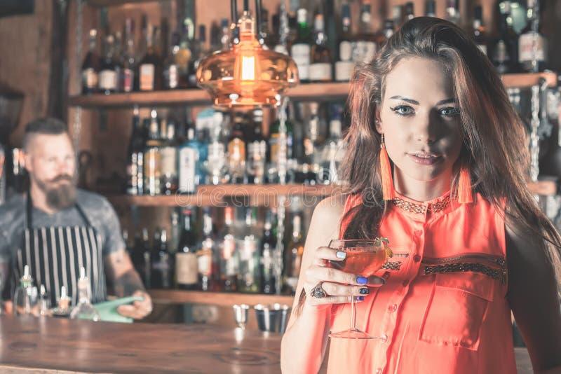 A menina bonita está bebendo um cocktail com o vapor do gelo na barra imagens de stock