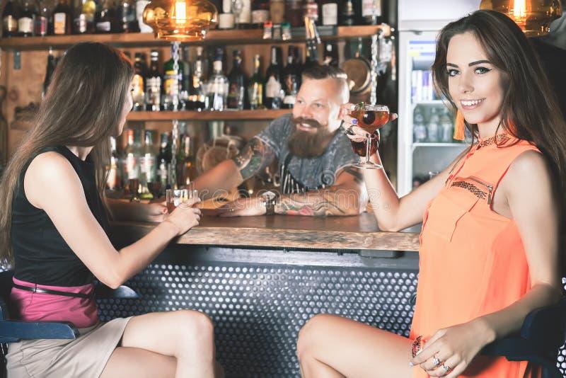 A menina bonita está bebendo um cocktail na barra fotografia de stock royalty free