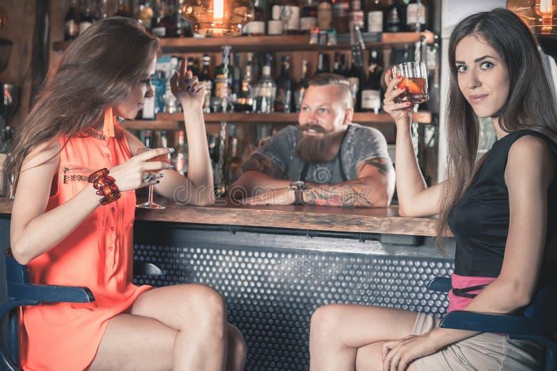 A menina bonita está bebendo um cocktail na barra fotos de stock