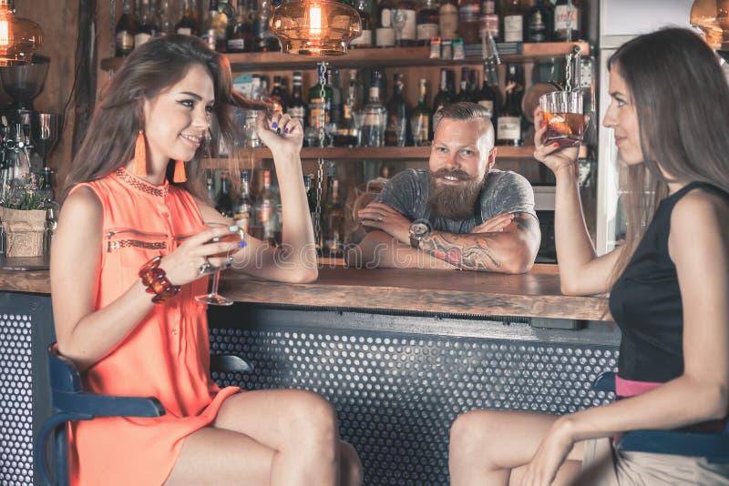 A menina bonita está bebendo um cocktail na barra foto de stock royalty free