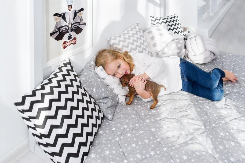 A menina bonita está encontrando-se com o cachorrinho do cão do bassê na cama fotos de stock royalty free
