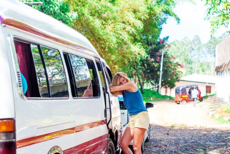 A menina bonita está estando de inclinação em uma janela do minibus imagens de stock