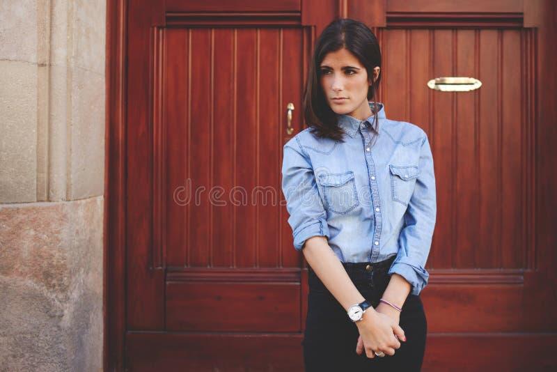 A menina bonita está estando na frente da porta de madeira, senhora lindo que levanta a um fotógrafo Sessão de foto elegante do r fotos de stock royalty free