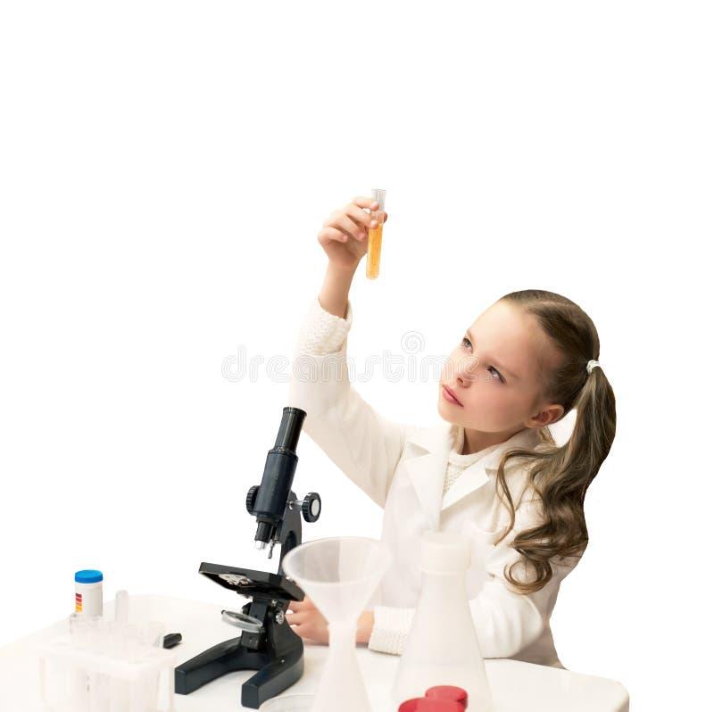 A menina bonita está fazendo experiências da ciência e está jogando a sagacidade foto de stock
