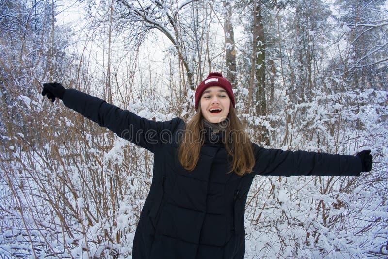 A menina bonita está feliz na floresta do inverno fotografia de stock