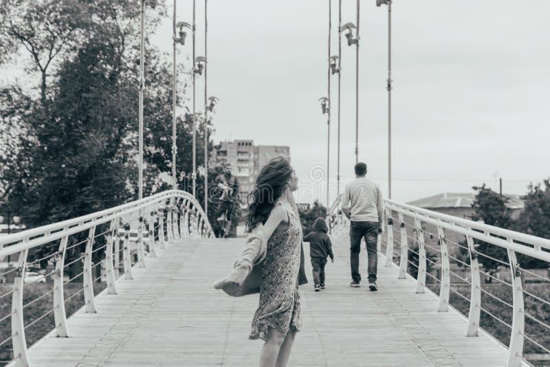 A menina bonita está na ponte, o vento funde em sua cara, desenvolvendo seu cabelo Sorrisos da menina foto preto e branco de danç imagens de stock