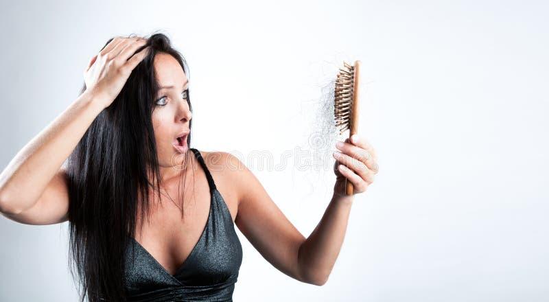 A menina bonita está olhando chocou-se a sua escova de cabelo foto de stock