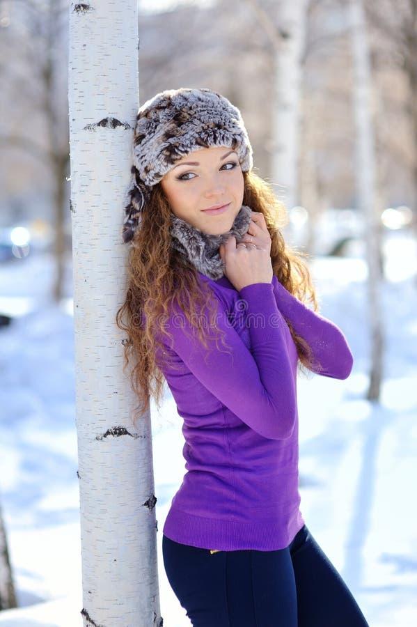 A menina bonita está perto do vidoeiro no inverno fotografia de stock