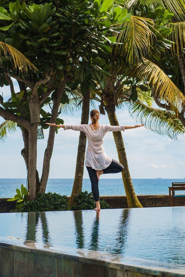 A menina bonita está praticando a ioga, meditação, estando a pose em um pé da parte traseira com paisagem do oceano em Indonésia imagens de stock