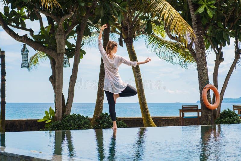 A menina bonita está praticando a ioga, meditação, estando a pose em um pé da parte traseira no recurso com paisagem do oceano imagem de stock royalty free