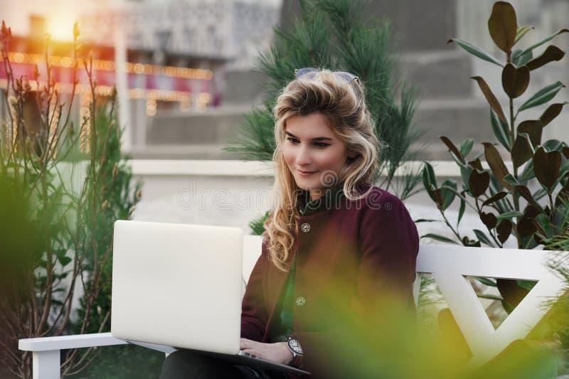 A menina bonita está sentando-se em um banco com um portátil em suas mãos em uma rua fresca com a cidade Um trabalho do concei foto de stock royalty free