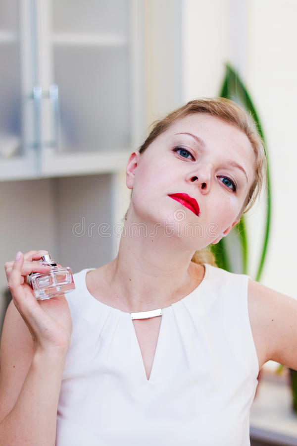 A menina bonita está testando um perfume novo imagens de stock