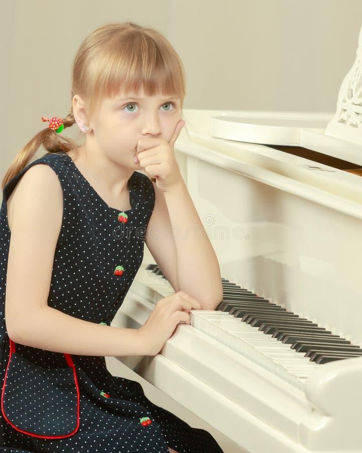 A menina bonita est? jogando em um piano de cauda branco imagens de stock royalty free