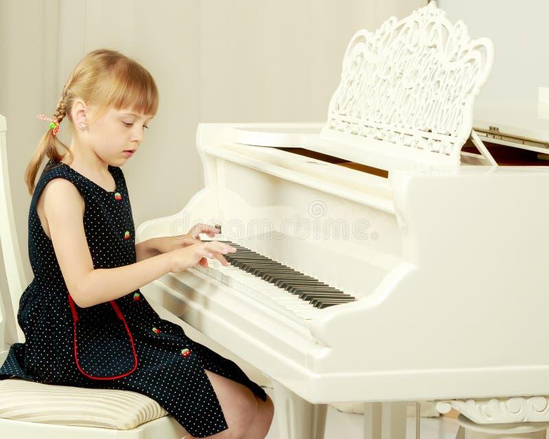 A menina bonita est? jogando em um piano de cauda branco imagem de stock