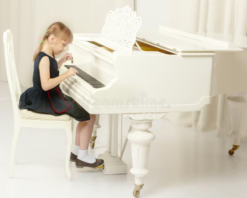 A menina bonita est? jogando em um piano de cauda branco fotos de stock
