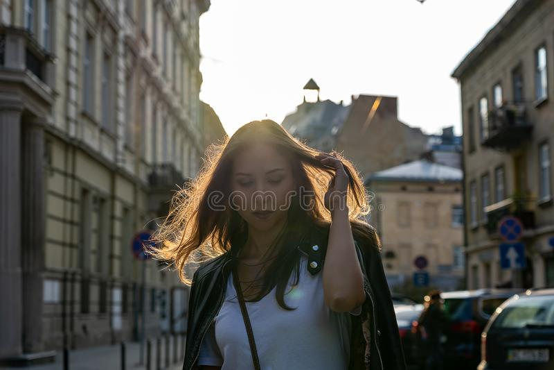 A menina bonita est? olhando para baixo Sessão fotográfica da forma da rua em uma rua da cidade com o luminoso do sol em um cabel foto de stock royalty free