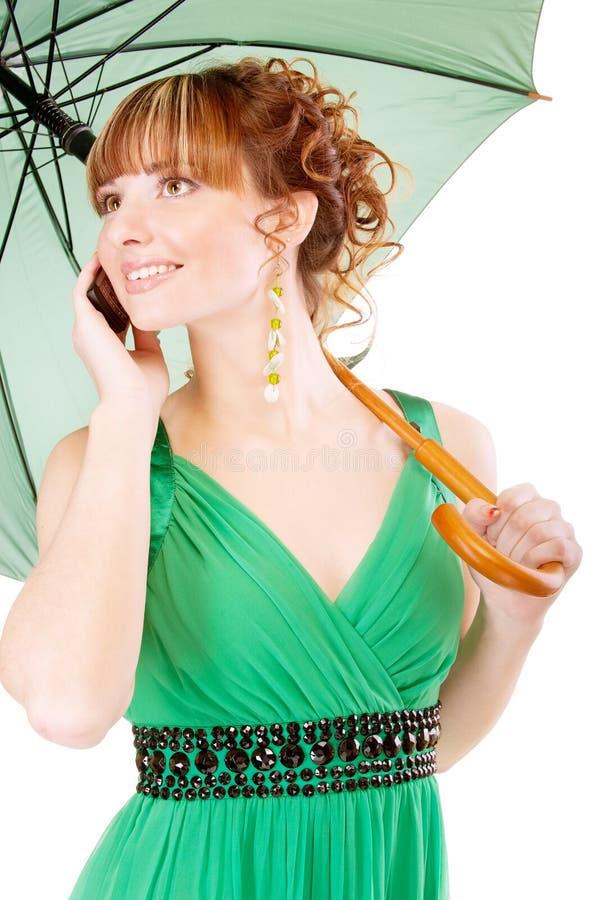 A menina bonita fala no telefone com o guarda-chuva verde imagem de stock