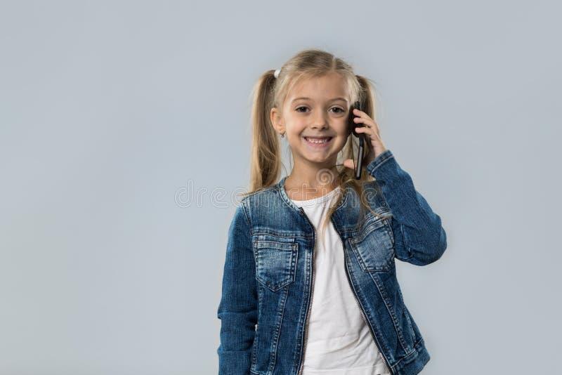 A menina bonita fala o revestimento de sorriso feliz das calças de brim do desgaste do telefonema esperto da pilha isolado fotos de stock