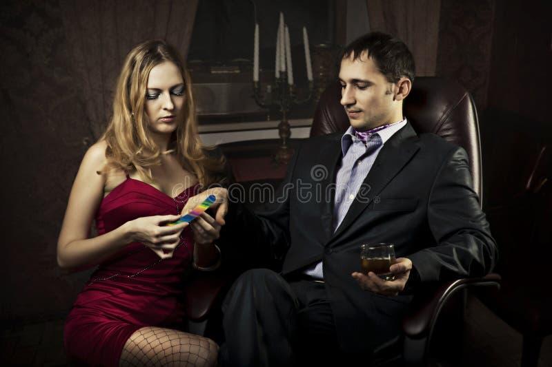 A menina bonita faz um homem rico do manicure fotos de stock royalty free