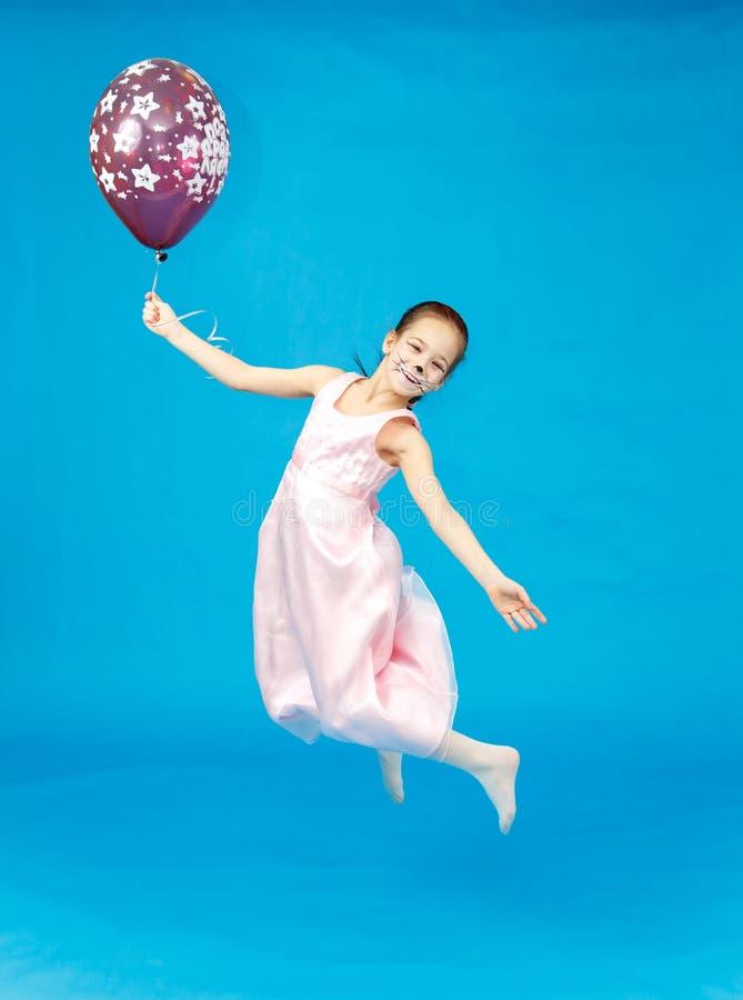 Menina bonita feericamente no voo cor-de-rosa do vestido com balão foto de stock