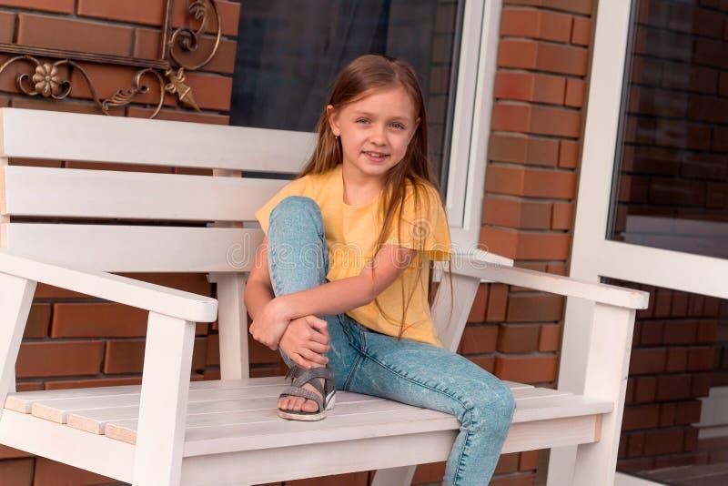 menina bonita feliz com o cabelo louro longo que veste a roupa ocasional que senta-se em um banco fotografia de stock