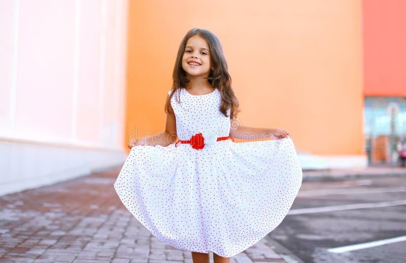 A menina bonita feliz mostra o divertimento branco do vestido e ter fotografia de stock