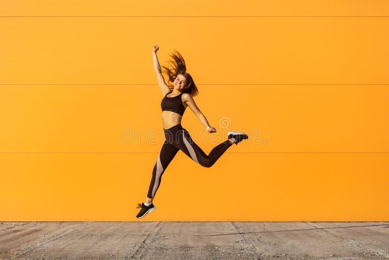 A menina bonita feliz nova que veste exercícios praticando do esporte do sporwear preto na manhã na rua, comemora o resultado do  fotografia de stock royalty free