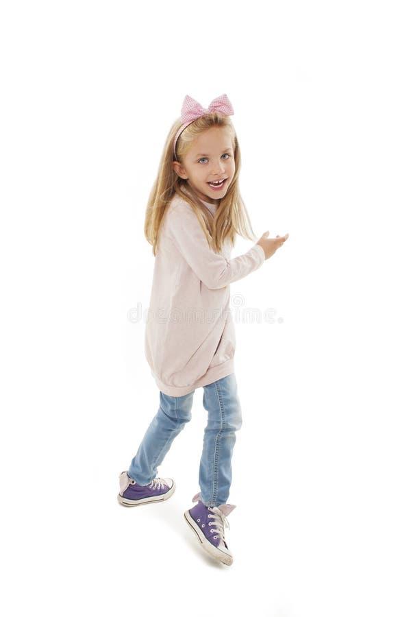 Menina bonita feliz que corre no fundo branco imagens de stock