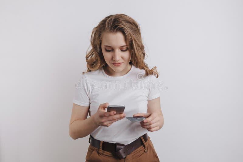 Menina bonita feliz que faz a compra em linha por seus telefone e cartão de crédito alaranjado foto de stock