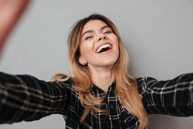 Menina bonita feliz que faz o selfie com telefone celular imagem de stock