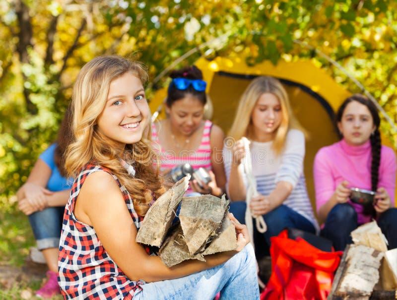 Menina bonita feliz que mantém a inflamação de madeira no acampamento fotos de stock royalty free