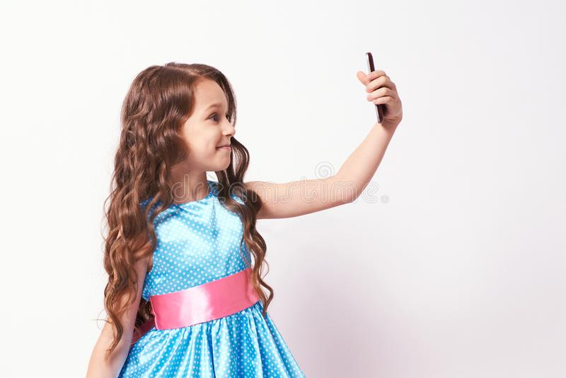 Menina bonita Foto no telefone Vestido azul luxúria foto de stock