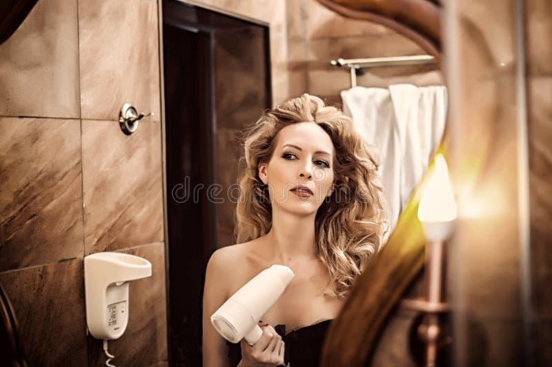 A menina bonita funde com um secador de cabelo e olha seu reflecti fotos de stock