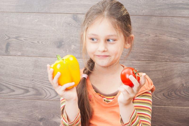 A menina bonita guarda legumes frescos foto de stock