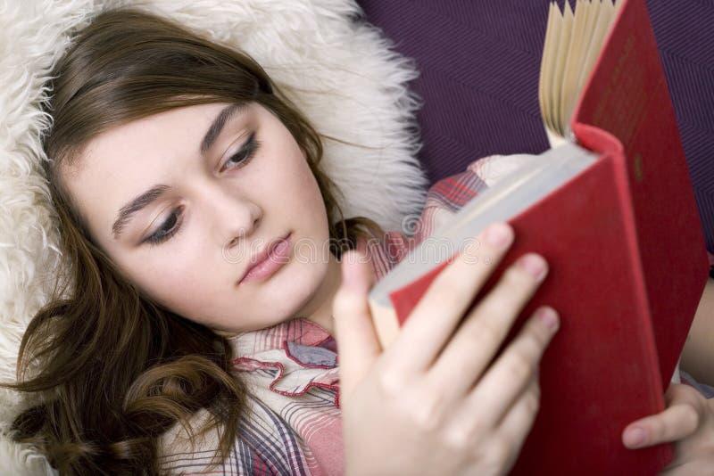 A menina bonita lê o livro fotografia de stock