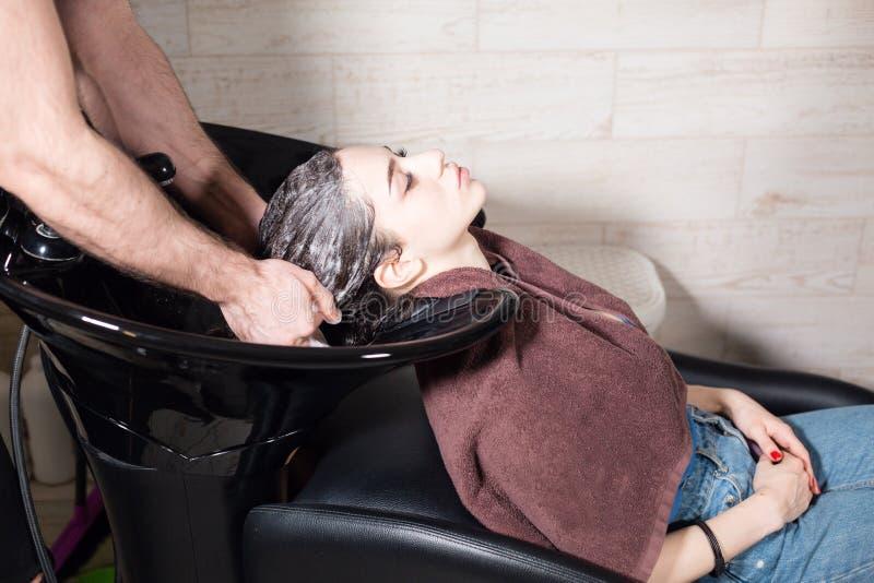 A menina bonita lava seu cabelo antes de um corte de cabelo em um salão de beleza cabelo que lava em um cabeleireiro, menina cauc imagens de stock royalty free