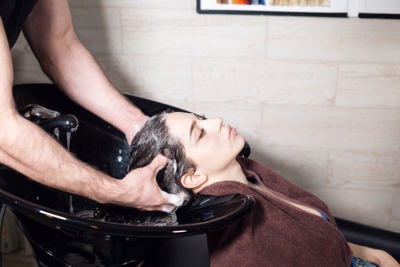 A menina bonita lava seu cabelo antes de um corte de cabelo em um salão de beleza cabelo que lava em um cabeleireiro, menina cauc foto de stock royalty free