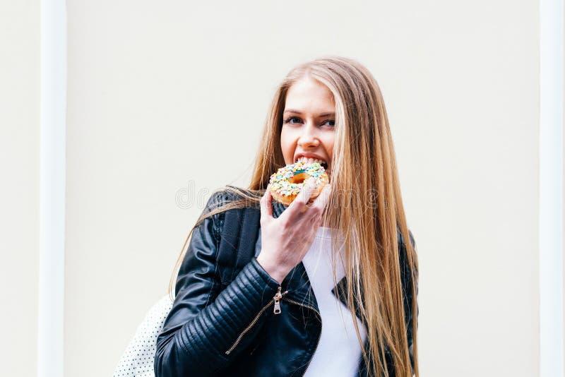 A menina bonita morde uma filhós deliciosa que anda nas ruas da cidade europeia Mola morna outdoor Fim acima fotos de stock royalty free