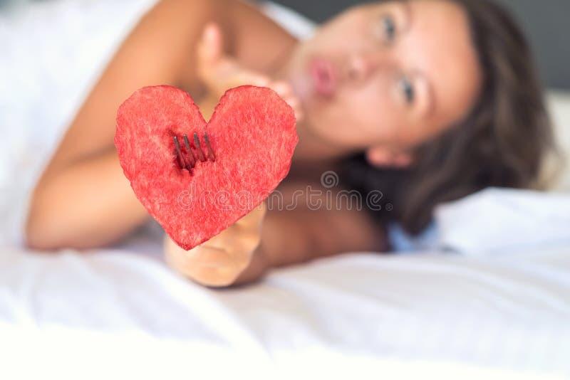 A menina bonita na cama dá o coração da melancia em uma forquilha imagem de stock