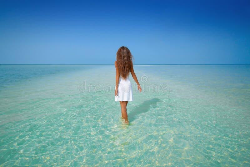 Menina bonita na caminhada branca do vestido na água na praia imagens de stock