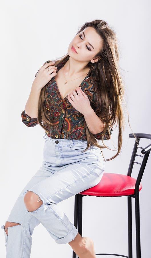 Menina bonita na camisa que senta-se em uma cadeira alta contra um fundo branco quente O vento em seu cabelo sorrisos foto de stock royalty free