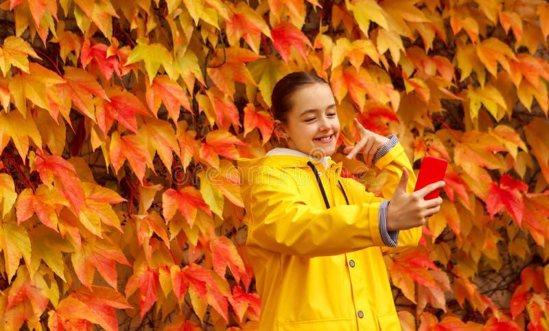 A menina bonita na capa de chuva amarela toma o selfie no fundo brilhante das folhas de outono fotos de stock royalty free